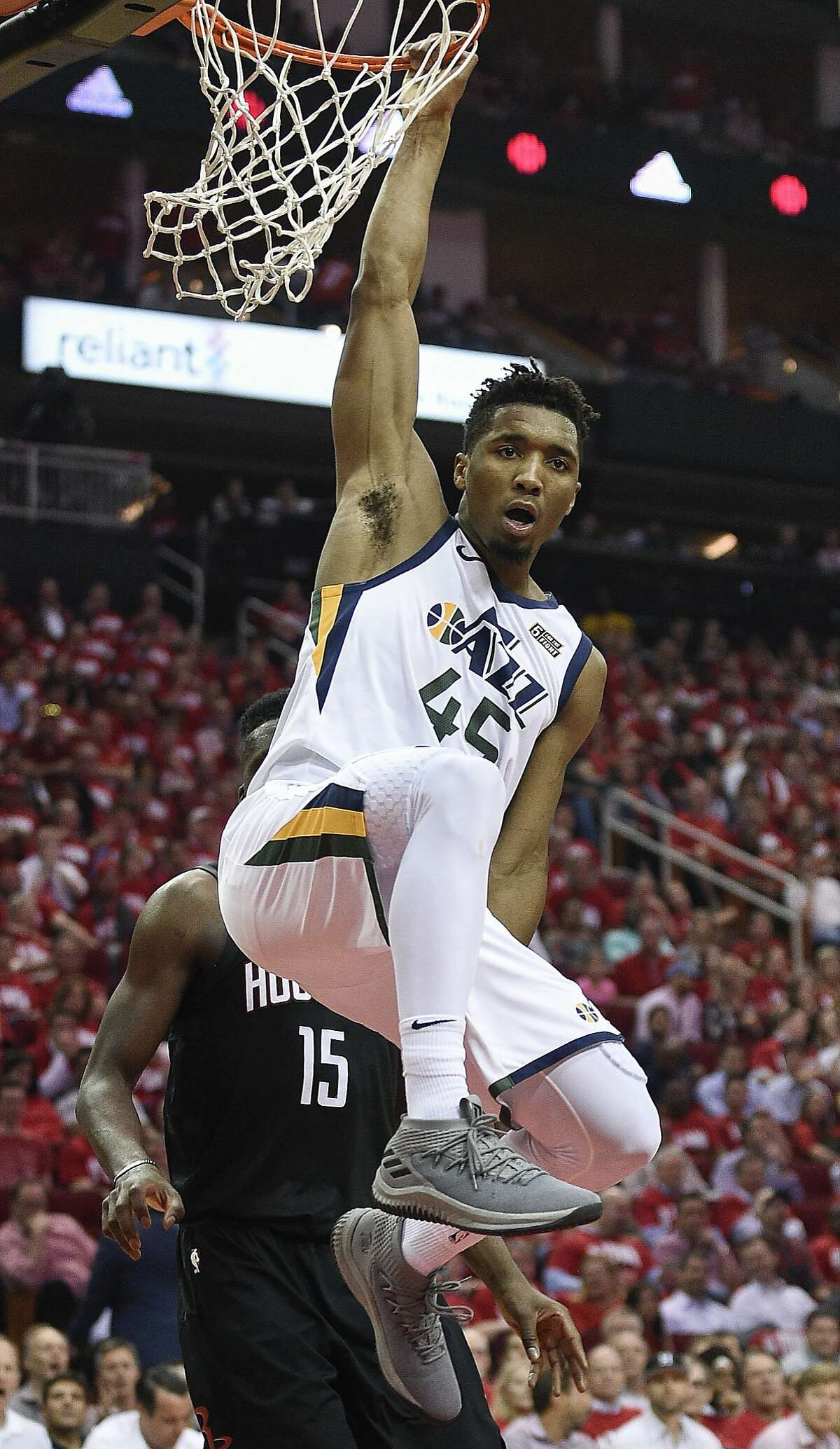 Utah Jazz guard Donovan Mitchell hangs from the rim after his dunk during the second half in Game 2 of an NBA basketball second-round playoff series against the Houston Rockets, Wednesday, May 2, 2018, in Houston. (AP Photo/Eric Christian Smith)