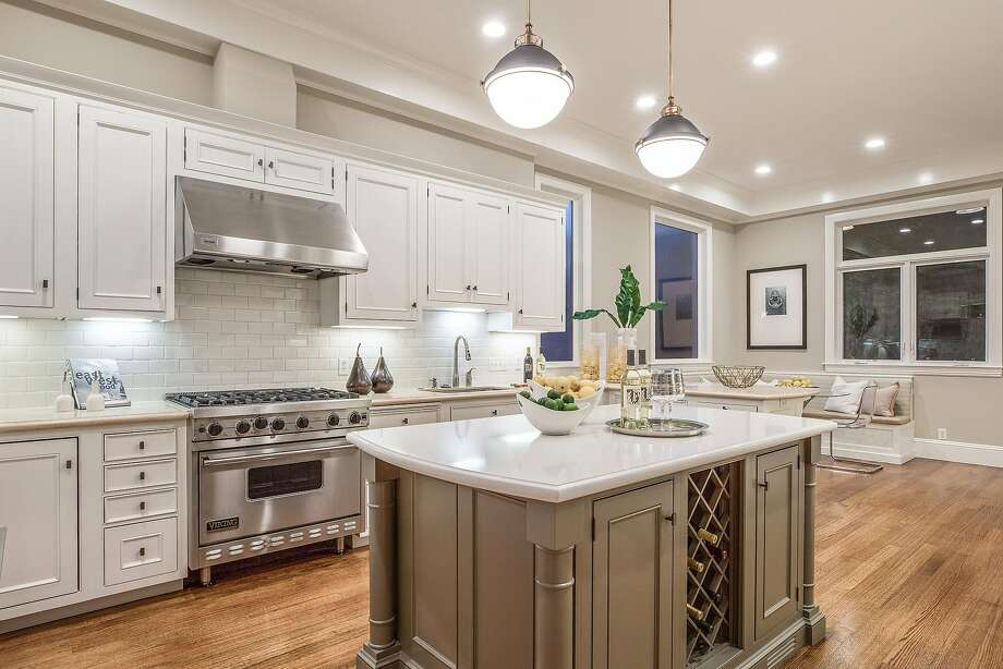 The chef's kitchen offers white cabinetry, task lights, and a professional range. Photo: Open Homes Photography