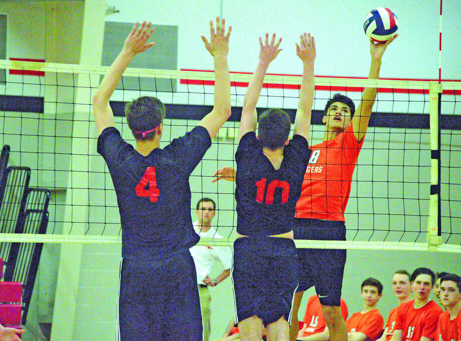 Edwardsville sophomore middle blocker Eric Epenesa, right, goes up for a kill during the second game of Thursday's Southwestern Conference match at Granite City.