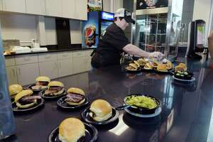 Maryrose Hart, managing partner Dinosaur BBQ Troy, puts out some sample sandwiches during a press event to unveil the newly rehabbed concession stand at the Times Union Center on Thursday, May 3, 2018, in Albany, N.Y. This is the first concession stand out of the seven to be updated. Each of the remaining concession stands will be worked on one at a time and plans are to have them all completed by November. Along with an updated look, the concession stands will have new grill areas so food can be prepared right at the stand. The Lia Lounge at the Times Union Center is also being rehabbed and when that opens in July it will feature a new bar area that will allow for more bartenders to work at, lessening the wait time for customers.  (Paul Buckowski/Times Union)