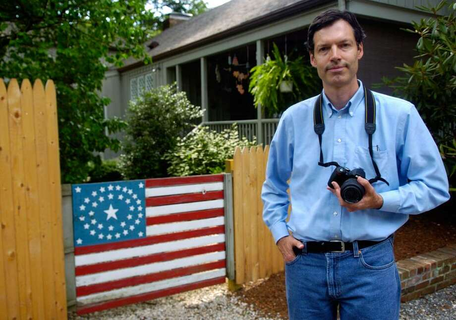 Robert Carley poses for a portrait in front of a flag painted on a fence at 2216 Post Road in Darien. Carley has been photographing American flags since Sept. 11, 2001. Photo: Lindsay Niegelberg / Connecticut Post