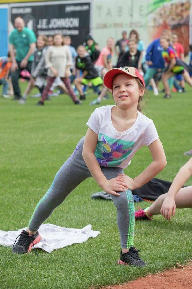 A student exercises as part of ACES Day at Dow Diamond on Wednesday morning. (Submitted photo) / Christopher Nowak - Michigan Fitness Foundation