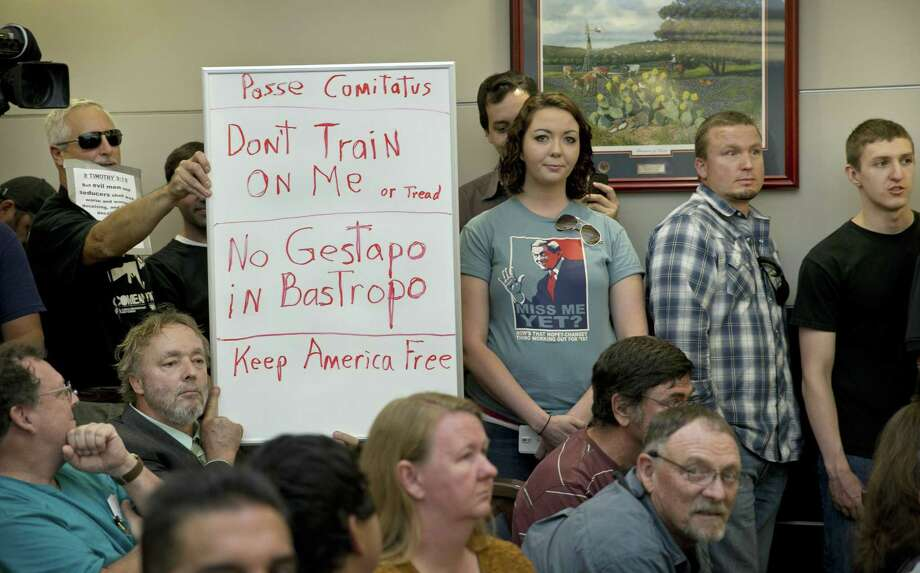 Bob Welch, standing at left, and Jim Dillon, hold a sign at a public hearing about the Jade Helm 15 military training exercise in Bastrop, Texas, Monday April 27, 2015. (Jay Janner/Austin American-Statesman via AP)  AUSTIN CHRONICLE OUT, COMMUNITY IMPACT OUT, INTERNET AND TV MUST CREDIT PHOTOGRAPHER AND STATESMAN.COM, MAGS OUT Photo: Jay Janner, MBO / Associated Press / Austin American-Statesman