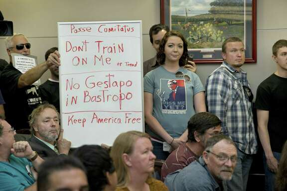 Bob Welch, standing at left, and Jim Dillon, hold a sign at a public hearing about the Jade Helm 15 military training exercise in Bastrop, Texas, Monday April 27, 2015. (Jay Janner/Austin American-Statesman via AP)  AUSTIN CHRONICLE OUT, COMMUNITY IMPACT OUT, INTERNET AND TV MUST CREDIT PHOTOGRAPHER AND STATESMAN.COM, MAGS OUT