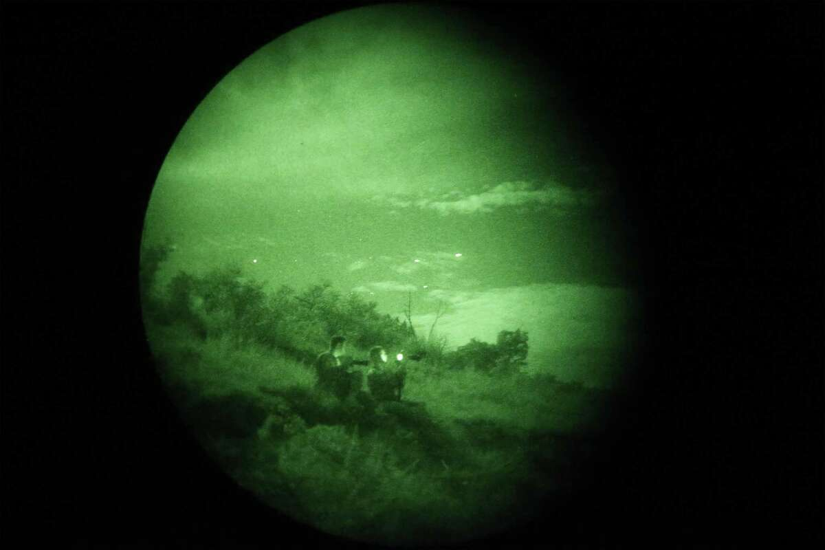 As seen through night vision goggles, two enlisted officers from the U.S. Army Special Operations Public Affairs Office watch C-17 transports (seen as white dots in the sky) fly overhead around 11 p.m. on Tuesday, Aug. 26, 2015 as part of a special warfare training exercise held at Camp Bullis.