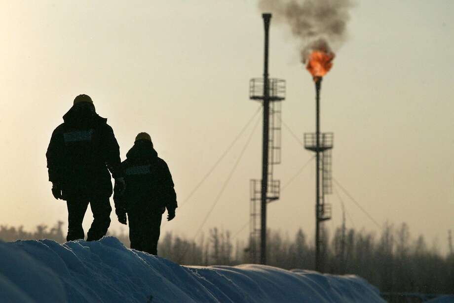 Two workers walk near a gas flare-off at the Yukos owned Mamontovskoye oil-field in the Khanty-Mansy region of the Russian Federation, Friday, December 17, 2004. Photo: DMITRY BELIAKOV, BLOOMBERG NEWS