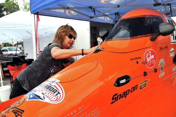 Kentucky-based driver Debby Mobley polishes her Formula Light racing craft as dusk began to set in at the Port Neches Park boat ramp on Thursday in Port Neches. Mobley will participate in time trials today and Saturday in hopes of securing a spot in Sunday's Thunder on the Neches boat race event. (Mike Tobias/The Enterprise)