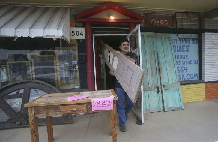 Old is Better Than New store owner Gabriel Galindo carries out some of his merchandise. Galindo specializes in salvaged architectural pieces that usually come from houses that are being torn down.