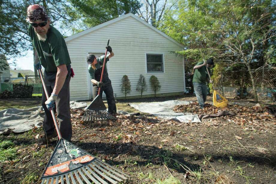 From left to right, Mark Gaffney, Robert Goodman, and David Johnson of Brennan Landscaping rake leaves onto tarps at the yard of a property in Schenectady, N.Y., on Tuesday, May 1, 2018. (Jenn March, Special to the Times Union) Photo: Jenn March / © Jenn March 2018 © Albany Times Union 2018