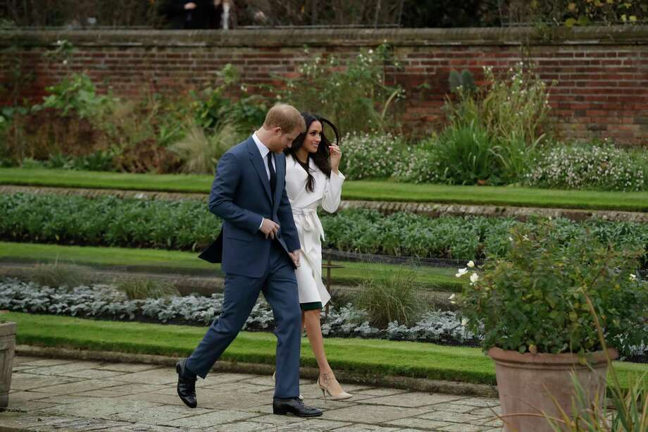 FILE - In this Nov. 27, 2017, file photo, Britain's Prince Harry and his fiancee Meghan Markle pose for photographers during a photocall in the grounds of Kensington Palace. Fans of the British royals will want to include castles, Westminster Cathedral and other sites connected to Queen Elizabeth II and her family on any trip to England. (AP Photo/Matt Dunham, File) Photo: Matt Dunham / Copyright 2018 The Associated Press. All rights reserved.
