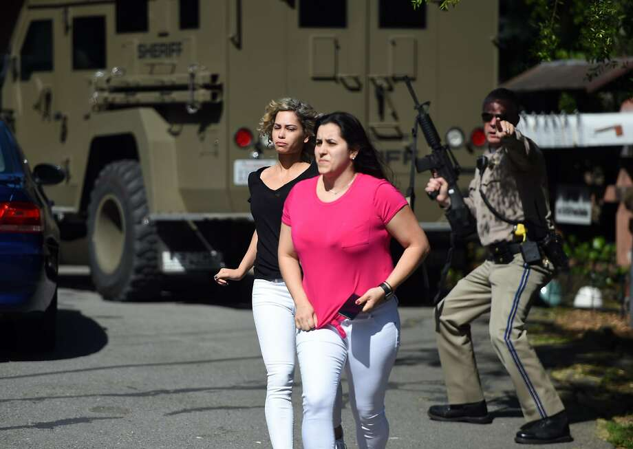 A law enforcement officer helps women escape the scene of a shooting Thursday in Mill Valley. Photo: Josh Edelson / Special To The Chronicle