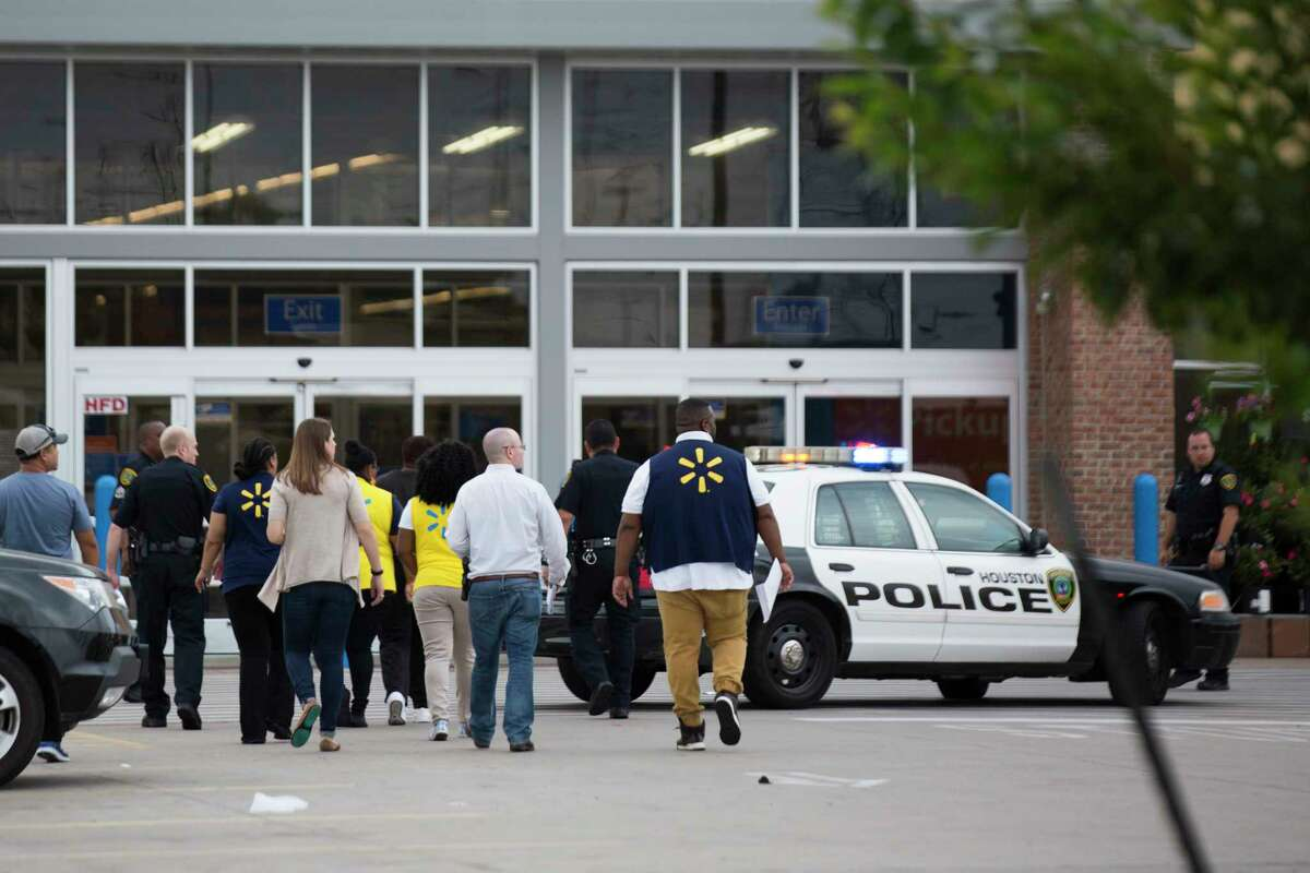 Accompanied by the Houston Police, Walmart employees enter the store after three masked suspects robbed the store, Friday, May 4, 2018, in Houston.