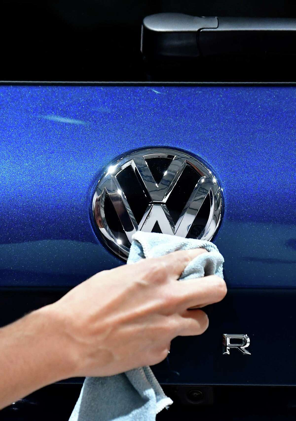 A staff member cleans a logo of an SUV VW Touareg on display ahead of the annual general meeting of German carmaker Volkswagen, in Berlin on May 3, 2018. / AFP PHOTO / Tobias SCHWARZTOBIAS SCHWARZ/AFP/Getty Images