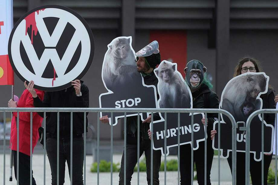 Animal rights activists hold up photos of monkeys and a Volkswagen AG (VW) logo during the automaker's annual general meeting in Berlin, Germany, on May 3, 2018. VW Chief Executive Officer Herbert Diess pledged to step up integrity and compliance efforts as part of the German manufacturer's deepest overhaul since the diesel-emissions scandal came to light in 2015. Photo: Krisztian Bocsi / Bloomberg / © 2018 Bloomberg Finance LP