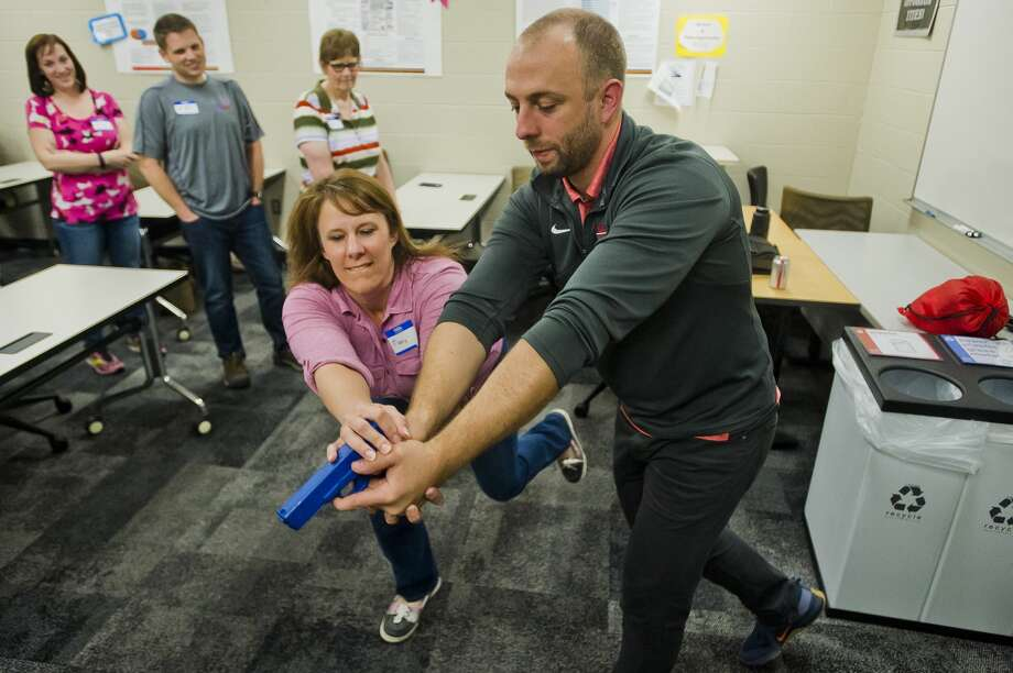 Mary Chavalia of Essexville, left, practices a technique for taking down an armed gunman after being shown the technique by Chris Schoenberg, right, during an active shooter training workshop on Friday, May 4, 2018 at Davenport University in Midland. (Katy Kildee/kkildee@mdn.net) Photo: (Katy Kildee/kkildee@mdn.net)