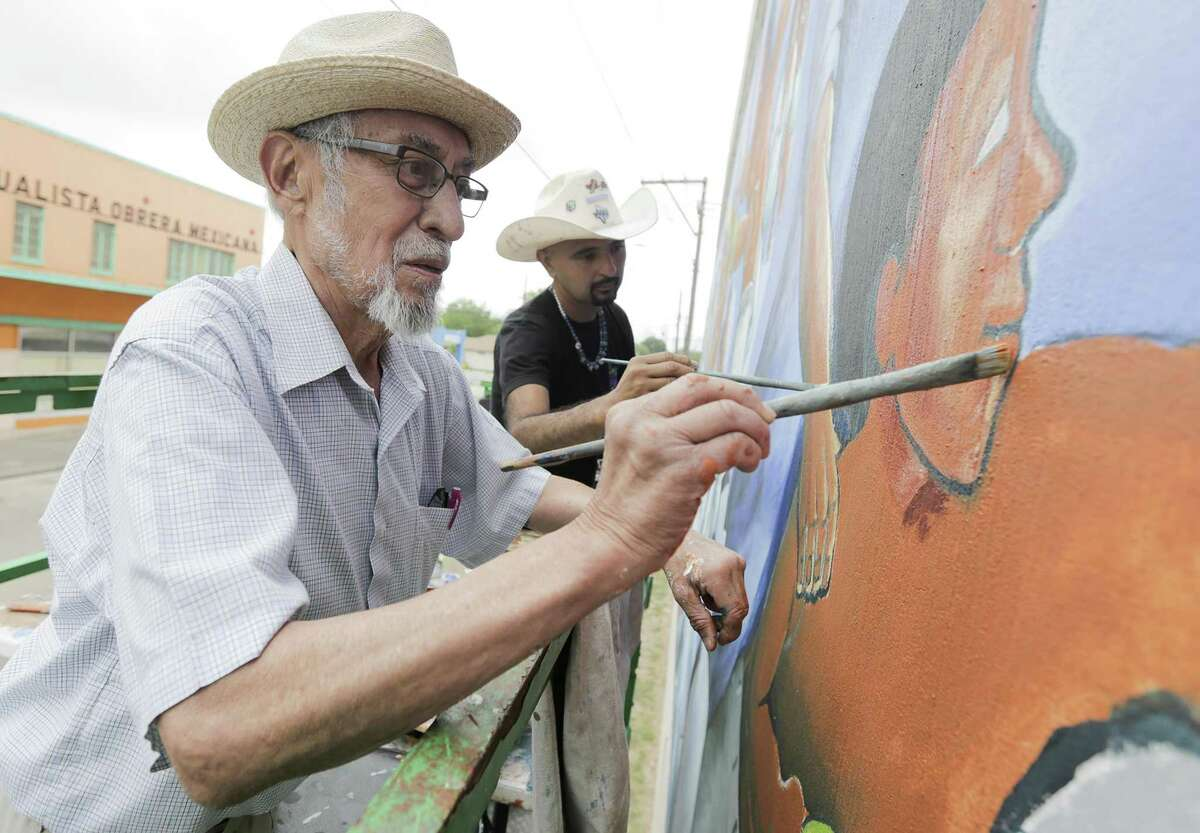 Leo Tanguma, left, and Gonzo 247 work on a mural that Tanguma painted in 1974 on Canal Street on Friday, May 4, 2018, in Houston. ( Elizabeth Conley / Houston Chronicle )