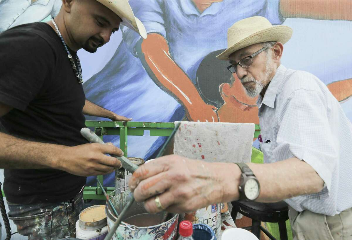 Leo Tanguma, right, and Gonzo 247 work on a mural that Tanguma painted in 1974 on Canal Street on Friday, May 4, 2018, in Houston. ( Elizabeth Conley / Houston Chronicle )