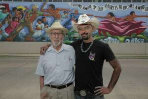 Leo Tanguma, left, and Gonzo 247 pose in front of a mural that Tanguma painted in 1974 on Canal Street on Friday, May 4, 2018, in Houston. ( Elizabeth Conley / Houston Chronicle )