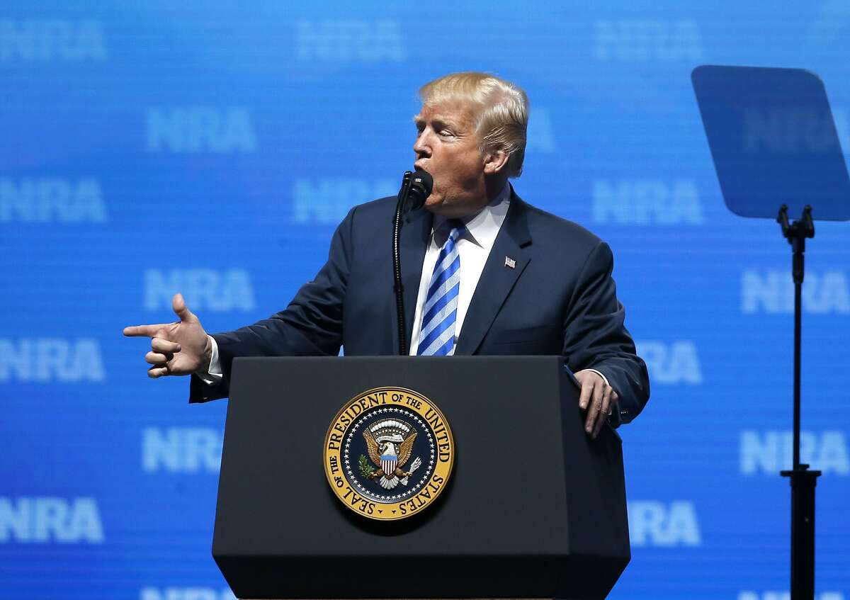 President Donald Trump uses a gun-shaped hand gesture to describe how terrorists shot victims in the 2015 Paris attacks as he speaks at the National Rifle Association annual convention in Dallas, Friday, May 4, 2018. (AP Photo/Sue Ogrocki)