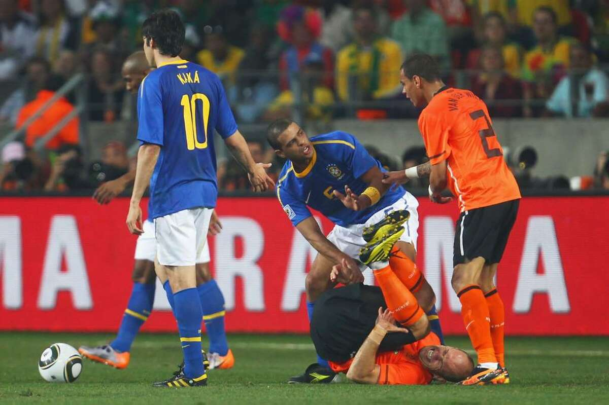 PORT ELIZABETH, SOUTH AFRICA - JULY 02: Felipe Melo of Brazil attempts to pull up to his feet the injured Arjen Robben of the Netherlands during the 2010 FIFA World Cup South Africa Quarter Final match between Netherlands and Brazil at Nelson Mandela Bay Stadium on July 2, 2010 in Nelson Mandela Bay/Port Elizabeth, South Africa. (Photo by Lars Baron/Getty Images) *** Local Caption *** Felipe Melo;Arjen Robben