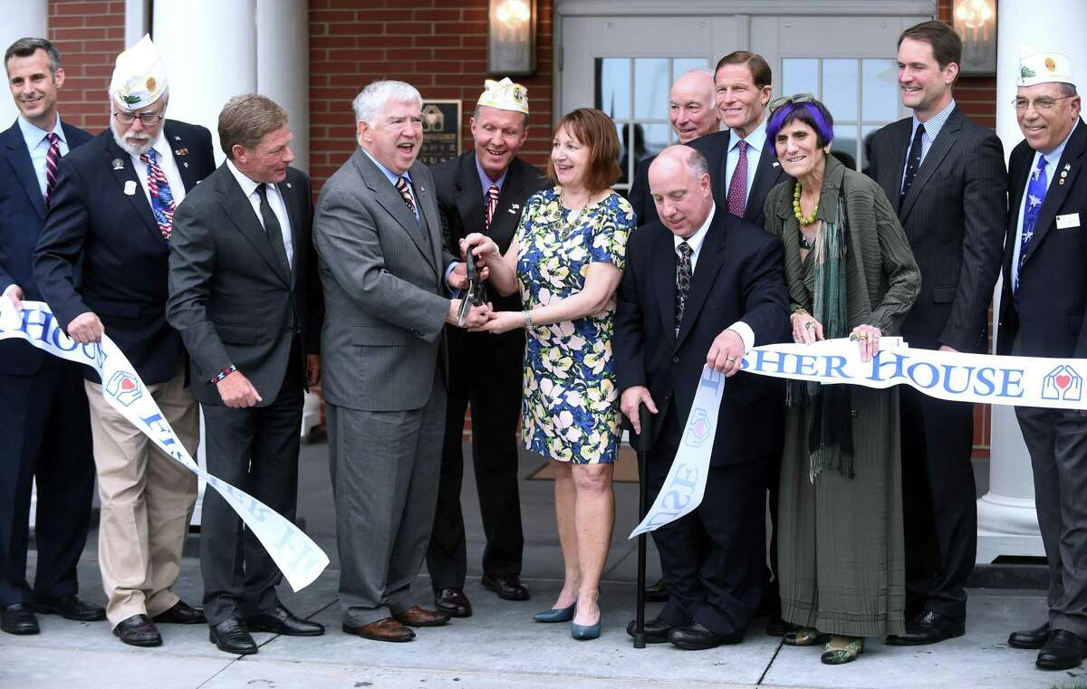From left, holding scissors, Kevin Creed, volunteer CEO, director and founder of the Friends of Fisher House Connecticut; Mark L. Rivard, Disabled American Veterans state commander, and Blue Star mother Susan Strobino, cut a ribbon to complete the dedication of the Veterans Administration Connecticut Fisher House on the grounds of the West Haven campus of the VA Connecticut Healthcare System on Friday.