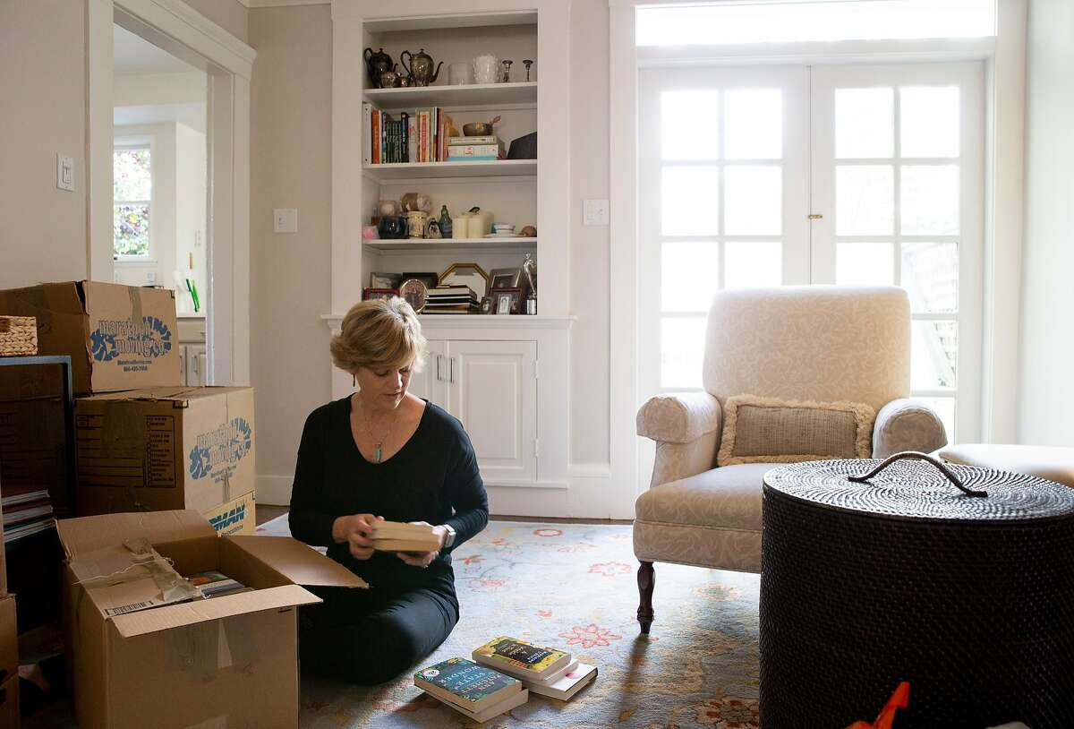 Linda Crowe unboxes her books at her new home, Thursday, May 3, 2018, in San Francisco, Calif.