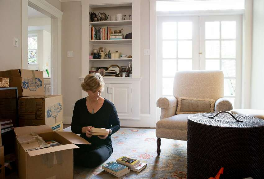 Linda Crowe unboxes her books at her new home in San Francisco. She took a well-paying job at IBM that makes up for the high costs of housing in the Bay Area.