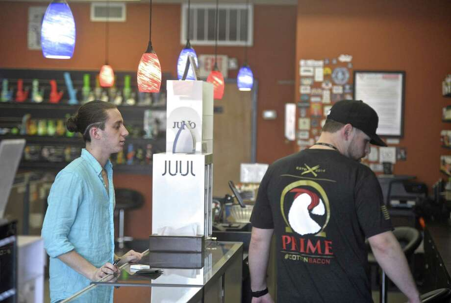 Jon Ambrose, right,  looks for a vaping liquid for Tyler Geragi, of Danbury, at the Twilight Vapor Shop in Danbury, Conn. Thursday, May 3, 2018. Photo: H John Voorhees III / Hearst Connecticut Media / The News-Times