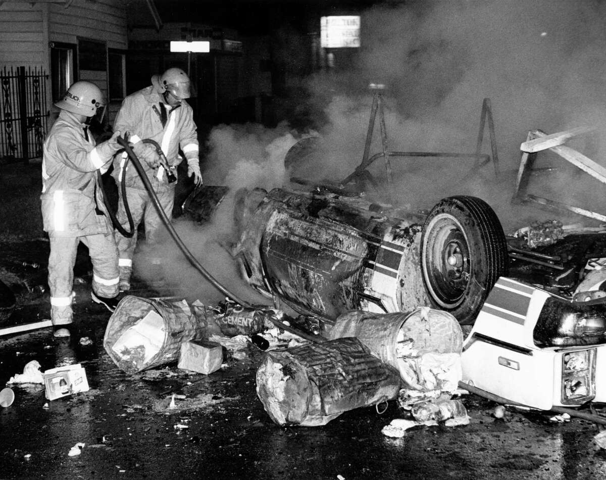 05/07/1978 - Houston firemen put out fire of burning car flipped during a riot that began in nearby Moody Park.