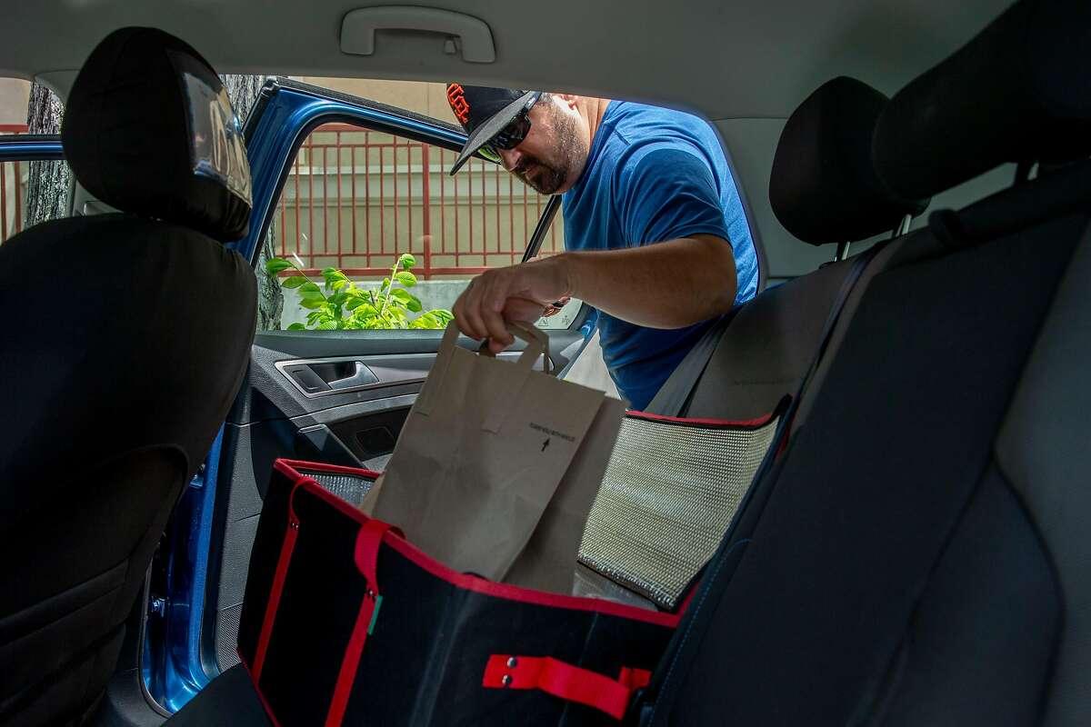 Aaron Powell delivers food using Doordash, Thursday, May 3, 2018, in Berkeley, Calif.