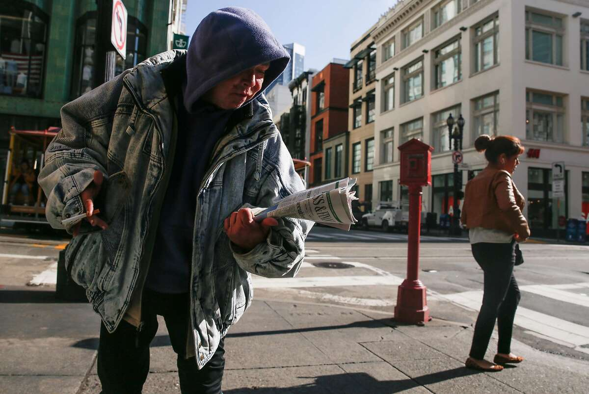 Amy, a homeless woman, walks down O'Farrell Street while carrying a newspaper Tuesday, Jan. 23, 2018 in San Francisco, Calif.