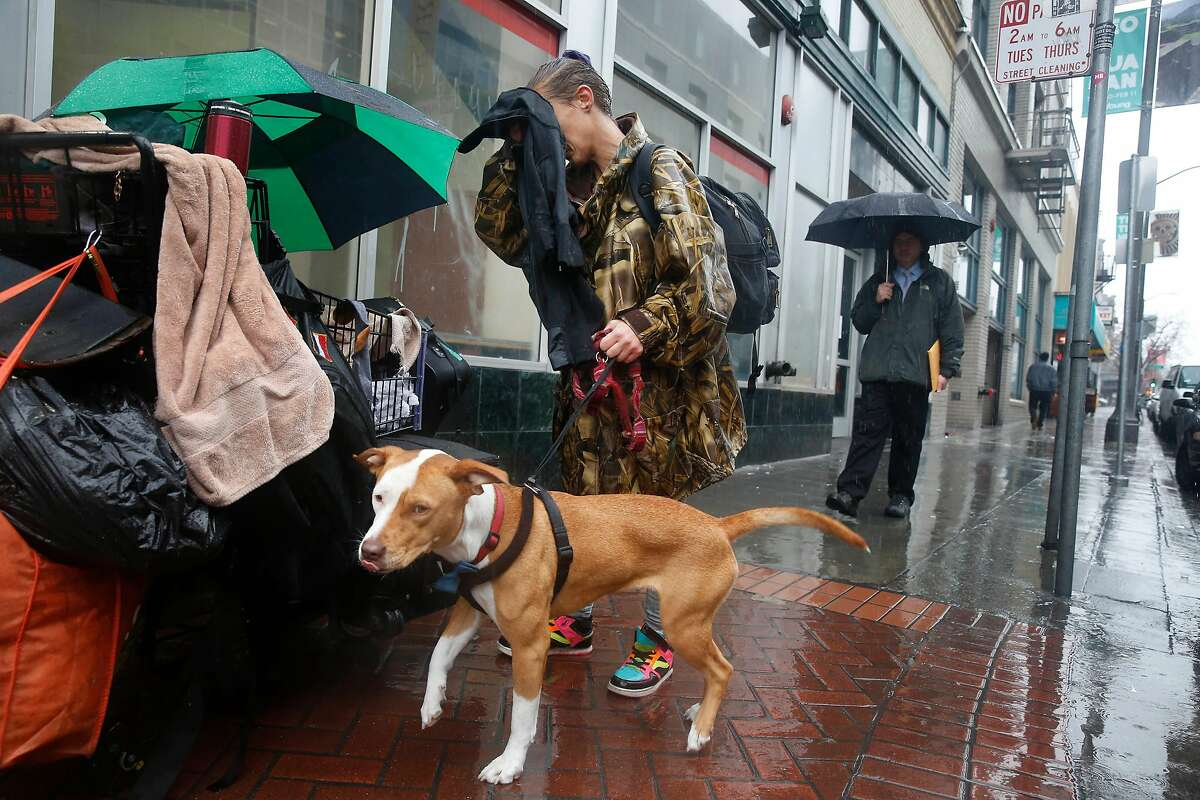 Amber Fina, who is homeless, wipes rain from her face as she stands with her dog, Ganja, on Grove Street before taking shelter from the rain in Burger King on Monday, January 8, 2018 in San Francisco, Calif.