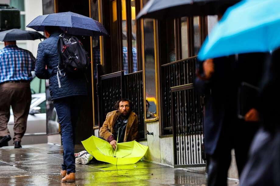 A homeless man sits with an umbrella on Powell Street in January. Photo: Gabrielle Lurie / The Chronicle