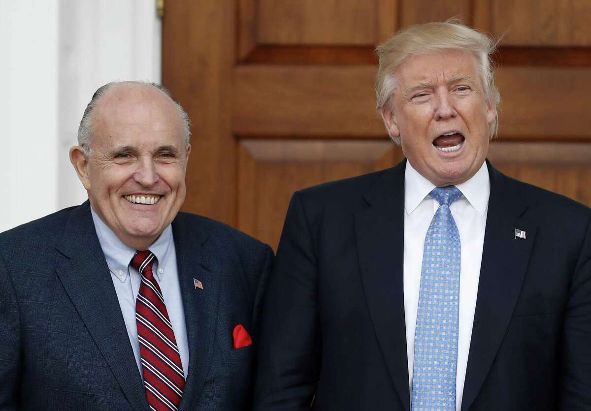 President Donald Trump calls out to media in 2016 as he and Giuliani pose for photographs as Giuliani arrives at the Trump National Golf Club Bedminster clubhouse in Bedminster, N.J..