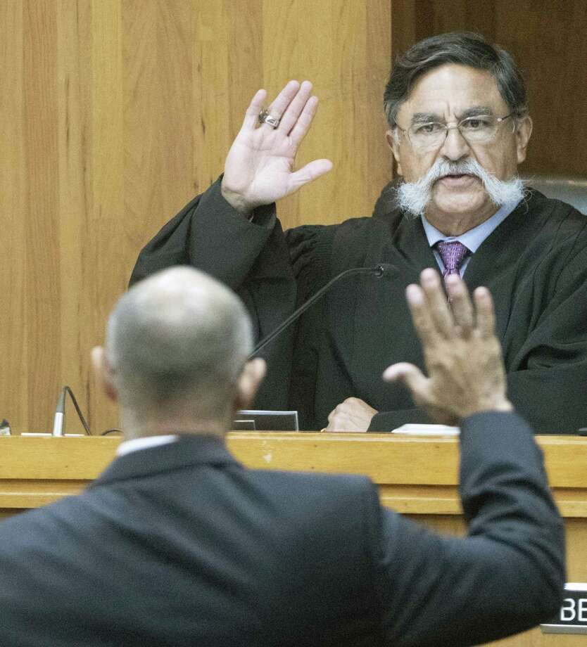 Judge J. Manuel Banales swears-in defendant Gilberto Escamilla during a sentencing hearing April 20 in the 107th state District Courtroom in Brownsville, Texas. Escamilla was sentenced to 50 years after entering two pleas of guilty for charges related to the theft of over $1 million of meats he stole and resold over two years through his position with Cameron County. Photo: Jason Hoekema /Associated Press / Jason Hoekema
