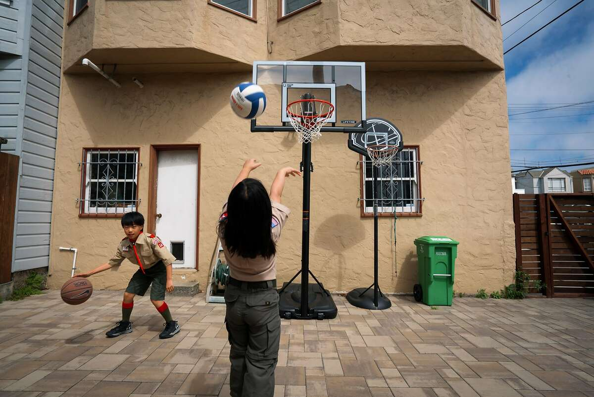 Hayden Fong, 11, (left) and Jordan Fong, 8, play basketball in the backyard of their home in San Francisco, Calif. on Thursday, May 3, 2018.