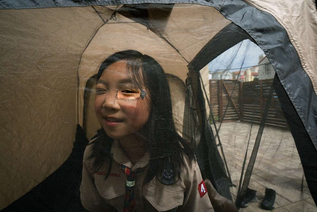 Jordan Fong, 8, peeks her eye through a hole in the tent at her home in San Francisco, Calif. on Thursday, May 3, 2018.