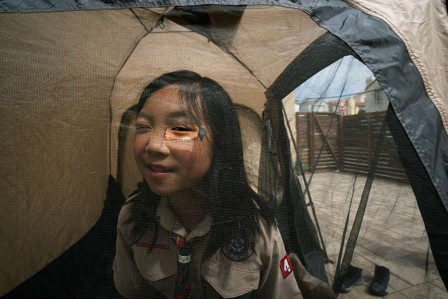 Third-grader Jordan Fong peeks through a hole in the tent screen. She would like to become an Eagle Scout. Photo: Sarahbeth Maney / Special To The Chronicle