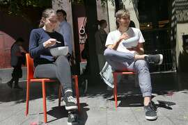 Samantha Thrush (left) and Austin Alphonse (right) have lunch on a sunny day at Mint Plaza on Friday, May 4, 2018 in San Francisco, Calif.