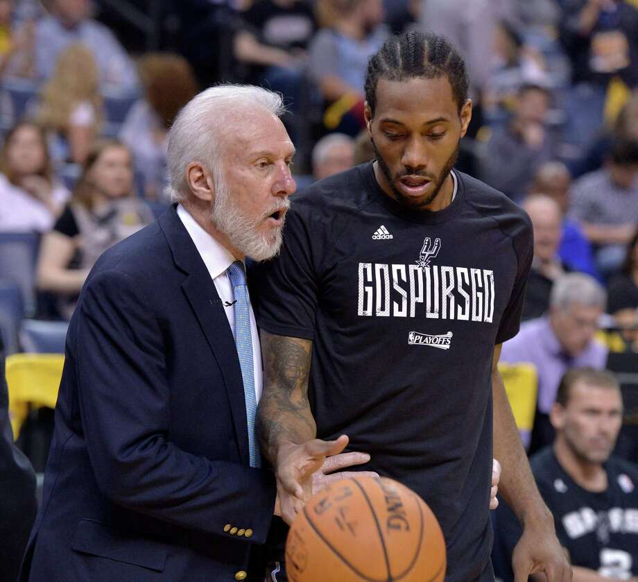FILE - In this April 22, 2017, file photo, San Antonio Spurs head coach Gregg Popovich, left, talks with San Antonio Spurs forward Kawhi Leonard during the second half of Game 4 in an NBA basketball first-round playoff series against the Memphis Grizzlies, in Memphis, Tenn. The absolute unwillingness to answer certain questions is part of the San Antonio Spurs' mystique. The Spurs just don't share much. So there is some unmistakable irony here that when it comes to the obviously fractured relationship between San Antonio and Kawhi Leonard, it's the Spurs who are the ones frustrated by the lack of answers.(AP Photo/Brandon Dill, File) Photo: Brandon Dill,  FRE / Associated Press / FR171250 AP