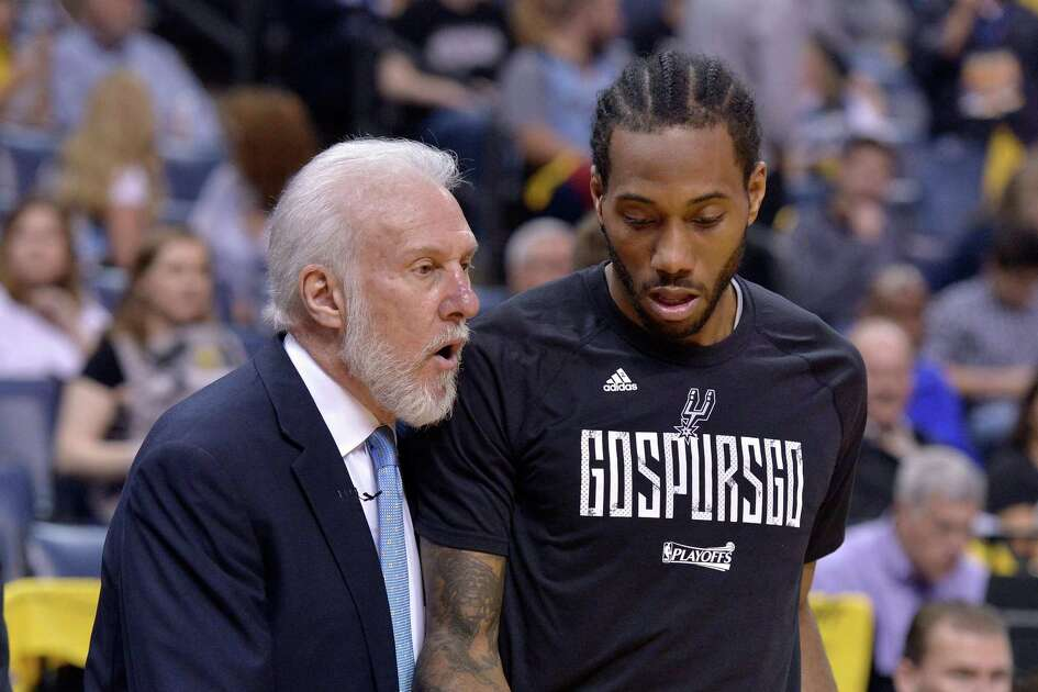 FILE - In this April 22, 2017, file photo, San Antonio Spurs head coach Gregg Popovich, left, talks with San Antonio Spurs forward Kawhi Leonard during the second half of Game 4 in an NBA basketball first-round playoff series against the Memphis Grizzlies, in Memphis, Tenn. The absolute unwillingness to answer certain questions is part of the San Antonio Spurs' mystique. The Spurs just don't share much. So there is some unmistakable irony here that when it comes to the obviously fractured relationship between San Antonio and Kawhi Leonard, it's the Spurs who are the ones frustrated by the lack of answers.(AP Photo/Brandon Dill, File)