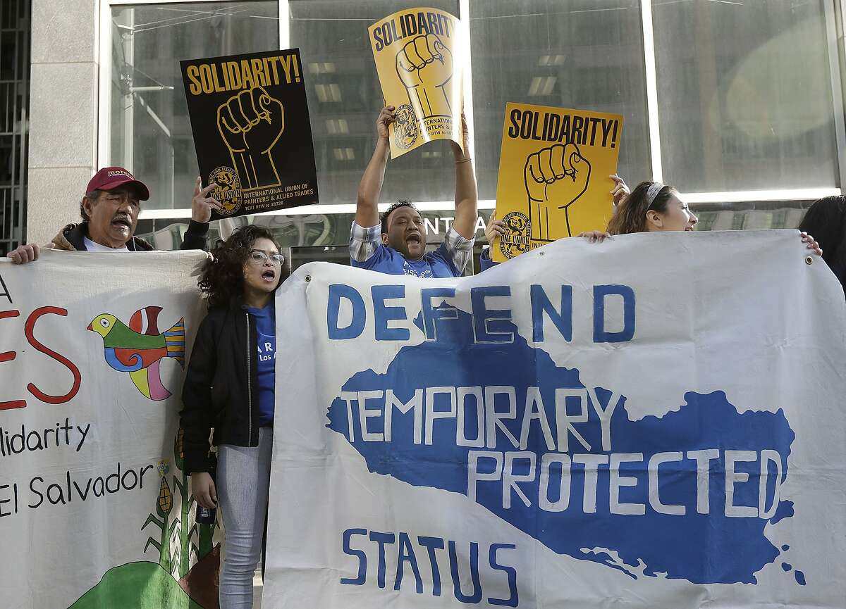 Supporters of temporary protected status immigrants hold signs and cheer at a rally in San Francisco, Monday, March 12, 2018.