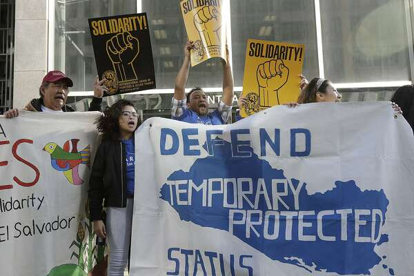 Supporters of temporary protected status immigrants hold signs and cheer at a rally before a news conference announcing a lawsuit against the Trump administration over its decision to end a program that lets immigrants live and work legally in the United States outside of a federal courthouse in San Francisco, Monday, March 12, 2018. Plaintiffs are alleging the decision to end temporary protected status for El Salvador, Haiti, Nicaragua and Sudan was racially motivated. (AP Photo/Jeff Chiu)