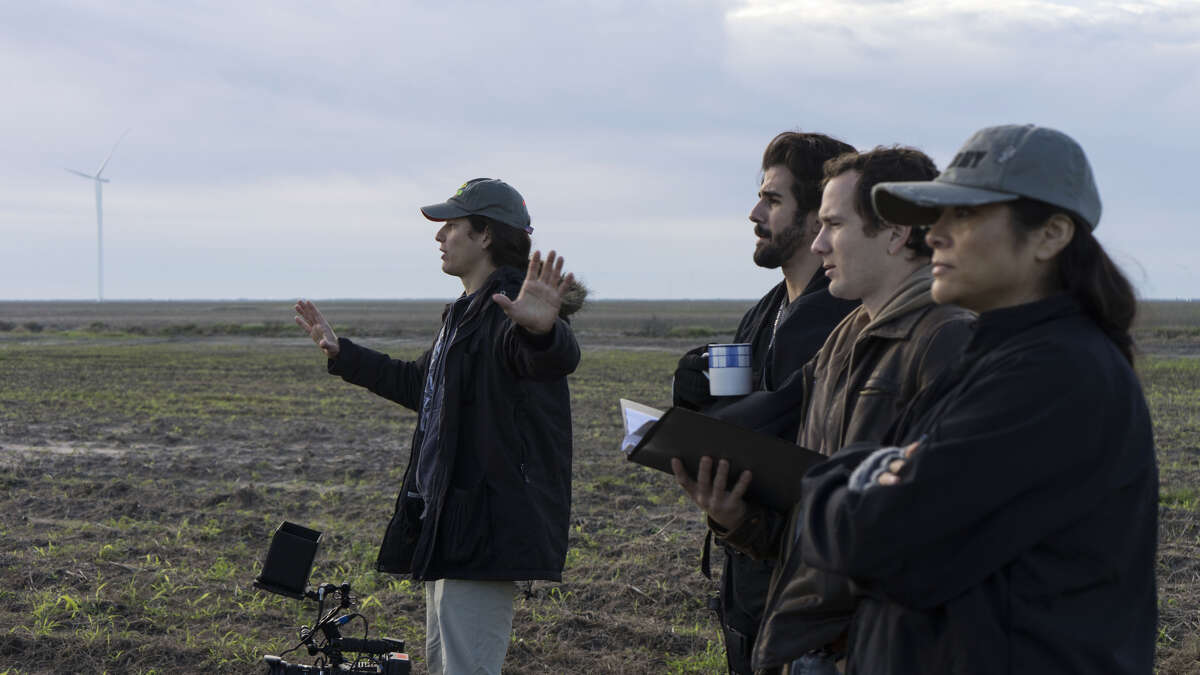 """David Blue Garcia (left) Directs a scene from the film """"Tejano"""" while (left to right) actors Adrian Gonzalez, Patrick Mackie and line producer Amy Soto look on."""
