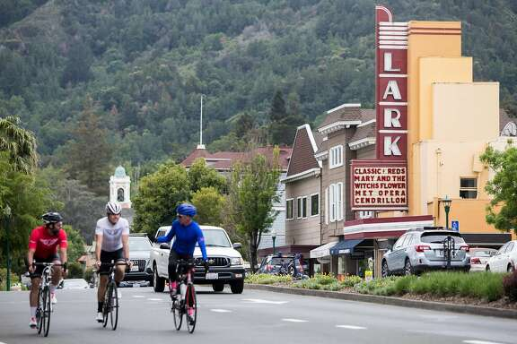 Cyclists bike past the Lark Theater Saturday, April 28, 2018 in Larkspur, Calif.