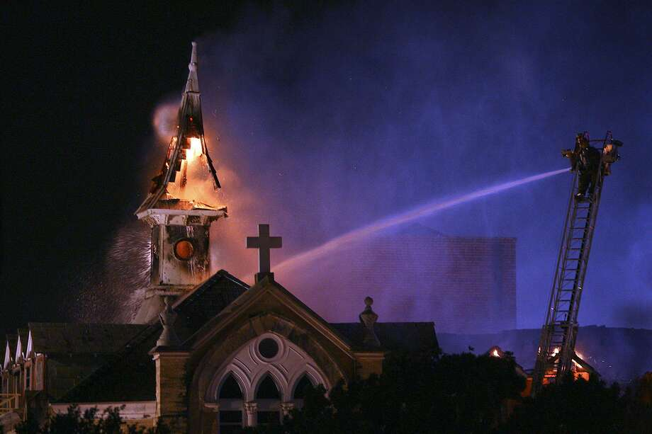 San Antonio firefighter spray water on the roof and a steeple of Our Lady of the Lake University which caught on fire Tuesday, May 6, 2008. AP Photo/San Antonio Express-News, Tom Reel) *** SAN ANTONIO OUT NO SALES MAGE OUT *** Photo: TOM REEL, MBO / AP / SAN ANTONIO EXPRESS-NEWS