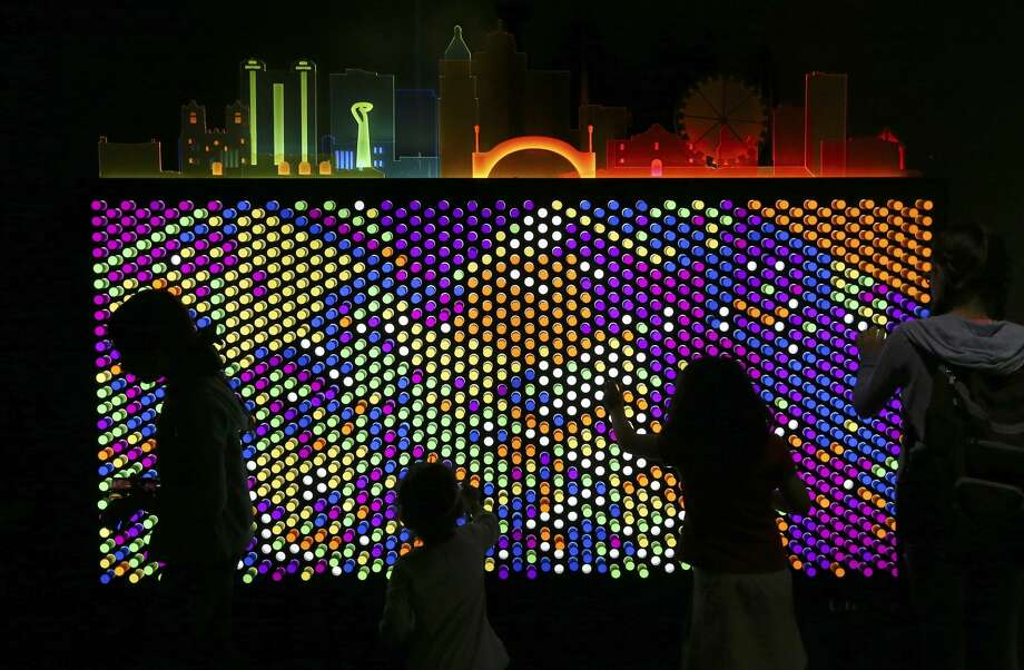 "Kids play in front of a ""lite brite""-type board at one of the Do-Seum's prototype exhibits on Friday, May 4, 2018. The prototypes offer the museum a way to get feedback from patrons - young and older - before including it as part of an exhibit which they are planning for the summer called ""Dream Tomorrow Today."" Area museums around town are open for free as part of the Tricentennial celebration called Arts for All day on Friday, May 4, 2018. The crowds at The DoSeum were a mix of patrons who knew about the free event which is held on behalf of the city's 300th anniversary. (Kin Man Hui/San Antonio Express-News) Photo: Kin Man Hui/San Antonio Express-News"