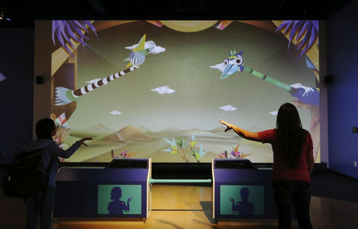 Trisha Garza (right) and her daughter, Isys (cq), interact with characters on a screen using their arms and hands at the Do-Seum on Friday, May 4, 2018. Area museums around town are open for free as part of the Tricentennial celebration called Arts for All day. The crowds at The DoSeum were a mix of patrons who knew about the free event which is held on behalf of the city's 300th anniversary. (Kin Man Hui/San Antonio Express-News)