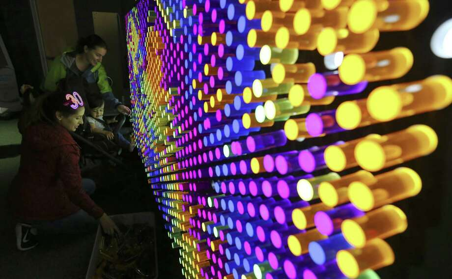 """Claudia Sanchez, left, with her 16-month old child, Enzo Ramos, and Lindsey Peters have fun at a """"lite brite""""-type board at one of the Do-Seum's prototype exhibits on May 4. Photo: Kin Man Hui /San Antonio Express-News / ©2018 San Antonio Express-News"""