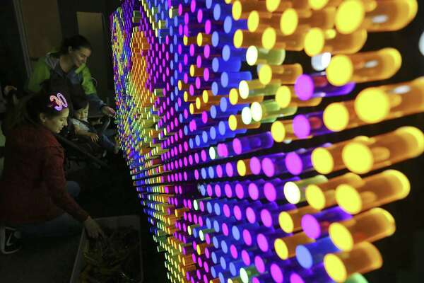 """Claudia Sanchez, left, with her 16-month old child, Enzo Ramos, and Lindsey Peters have fun at a """"lite brite""""-type board at one of the Do-Seum's prototype exhibits on May 4."""